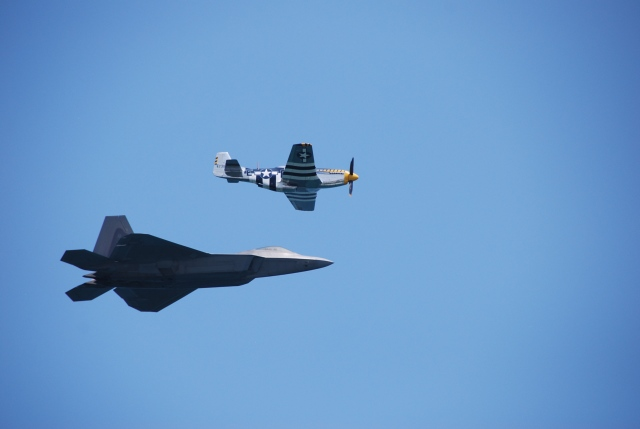 A thoroughly modern F-22 and a sixty year old P-51